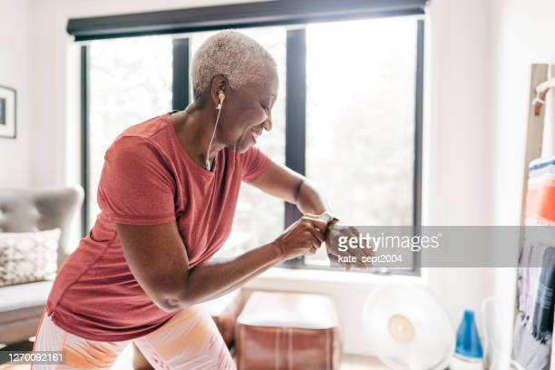 shot of beautiful senior women in sportswear looking on her watch - active seniors stock pictures, royalty-free photos & images