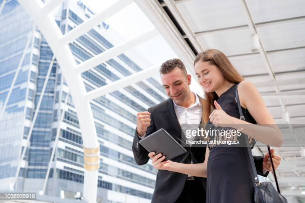 shot of business people celebrating sale volume after looking sale order in tablet - successor stock pictures, royalty-free photos & images