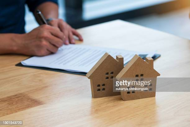 shot of businessman signs contract behind home model. - stock trader stock pictures, royalty-free photos & images