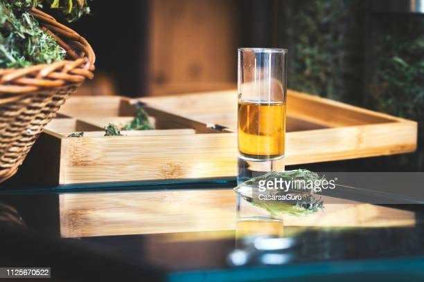 shot of cannabis liquor on table - hemp stock pictures, royalty-free photos & images