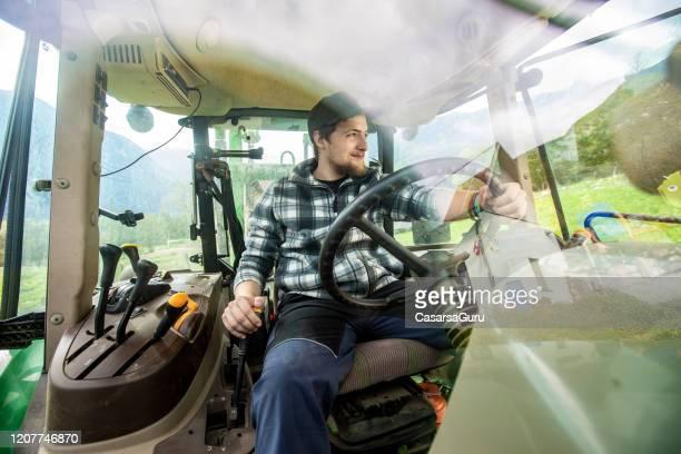 眺めを楽しむトラクターの正面窓から農民の息子のショット - ストック写真 - トラクター ストックフォトと画像