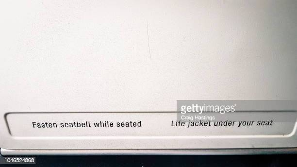Shot of fasten seat belts sign on tray table in flight