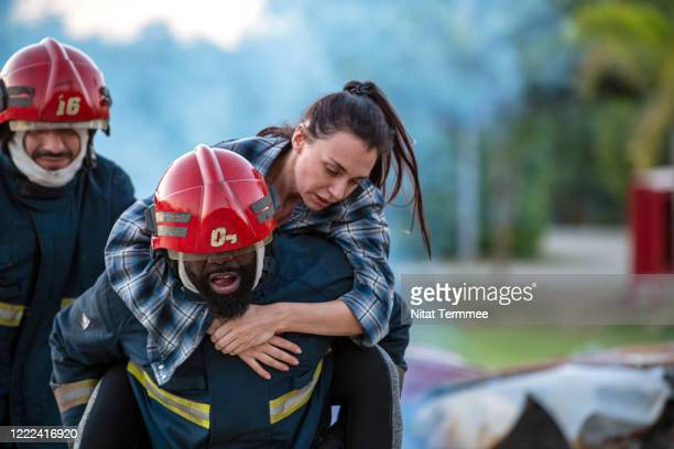 shot of firefighters rescue a woman carrying on his shoulder the road after an car accident. - rescue stock pictures, royalty-free photos & images