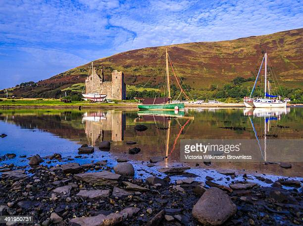 CONTENT] Shot of Lochranza Castle and two yachts reflected in the still waters of Loch Ranza Isle of Arran Scotland