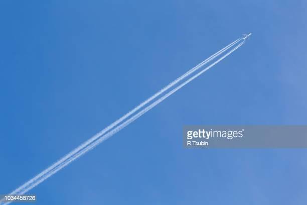 shot of long trail of jet plane on blue sky - trainée d'avion photos et images de collection