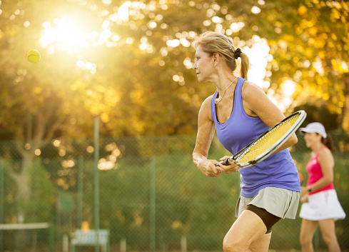 Shot of mature women playing tennis. 1095193638