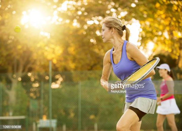 shot of mature women playing tennis. - tennis player stock pictures, royalty-free photos & images
