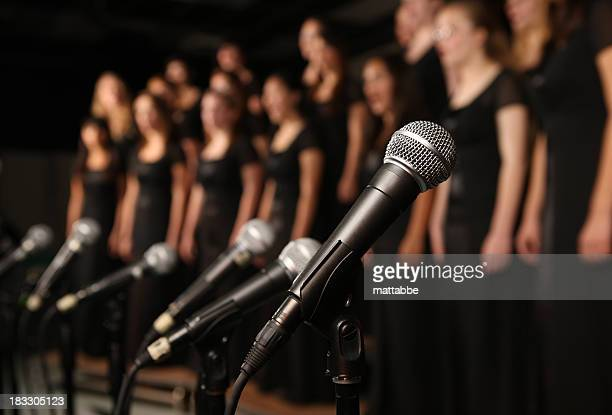 shot of microphones with choir in the background - singing stock pictures, royalty-free photos & images