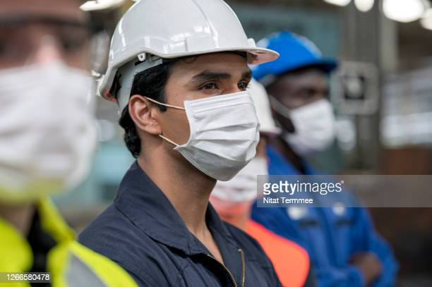 shot of multi-ethnic in heavy industry workers wearing face mask, helmet and jumpsuit. focus on maintenance engineer. - manufacturing stock pictures, royalty-free photos & images