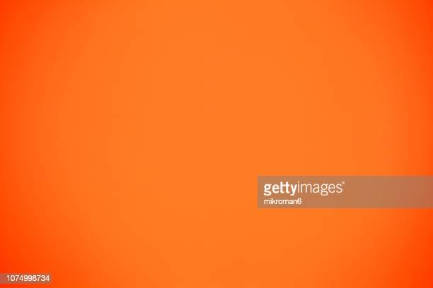 shot of orange colored paper background - arancione foto e immagini stock