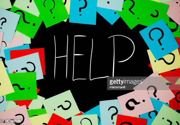 shot of question marks on colorful adhesive notes with help in the middle - help single word stock pictures, royalty-free photos & images