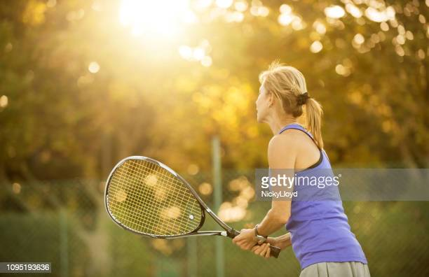 shot of senior woman playing tennis on court. - tennis stock pictures, royalty-free photos & images