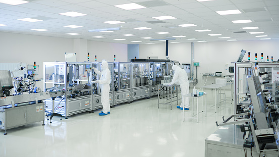 Shot Of Sterile High Precision Manufacturing Laboratory where Scientists in Protective Coverall's Use Computers and Microscopes, doing Pharmaceutics, Biotechnology and Semiconductor Research. 1087218888