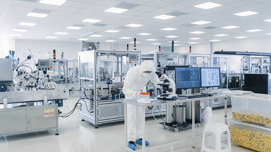 Shot of Sterile Pharmaceutical Manufacturing Laboratory where Scientists in Protective Coverall's Do Research, Quality Control and Work on the Discovery of new Medicine. 1087218874