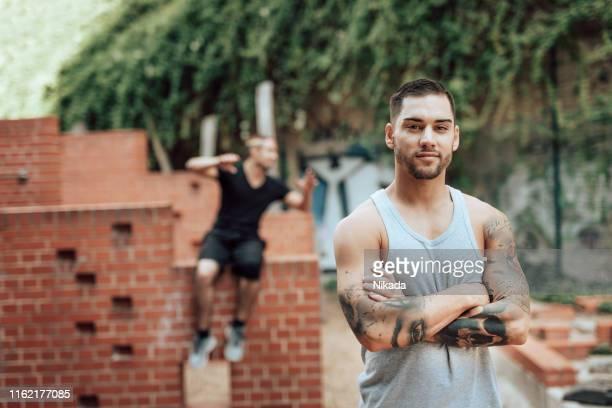 schuss von starkem jungen parkour-mann im urbanen raum - sportsperson stock-fotos und bilder