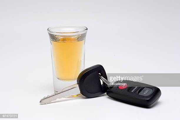 Shot of tequila next to car keys over a white background