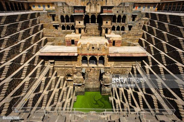 a shot of the incredible chand baori stepwell and it's temple, abhaneri, rajasthan, india - abhaneri stock photos and pictures