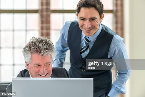 Tiro de dois Empresário falando sobre um monitor