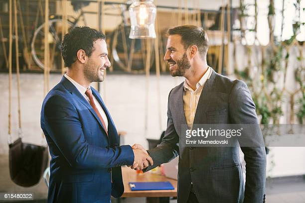 Shot of two businessmen shaking hands. Side view.