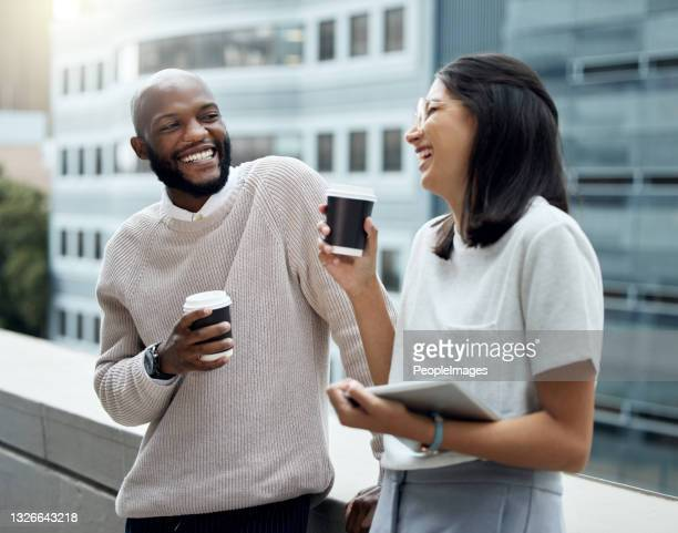 shot of two businesspeople drinking coffee together outside an office - casual clothing stock pictures, royalty-free photos & images
