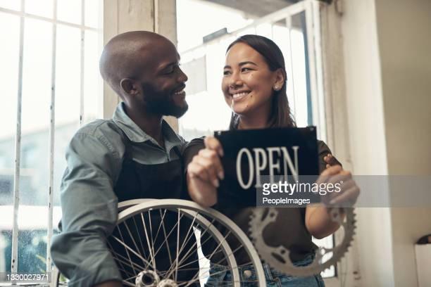 自転車店で一緒に立ち、開いた看板を持つ2人の若いビジネスオーナーのショット - クランクセット ストックフォトと画像