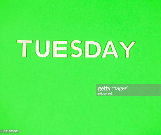 shot of yellow paper background with word tuesday - tuesday stock pictures, royalty-free photos & images