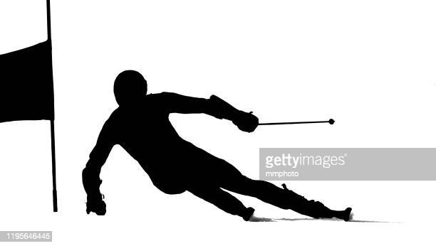 shot of young adult alpine skier racing giant slalom, silhouette, isolated on white - alpine skiing stock pictures, royalty-free photos & images