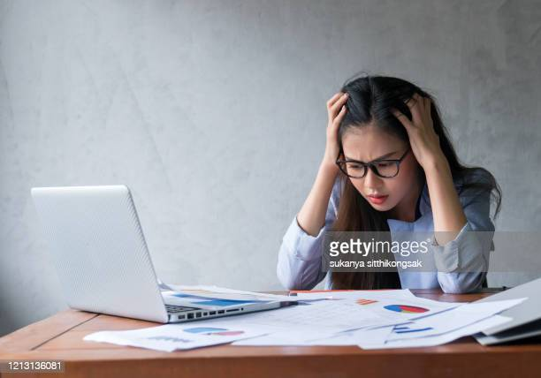shot of young businesswoman looking bored while working at her desk in a modern office. - information overload stock pictures, royalty-free photos & images