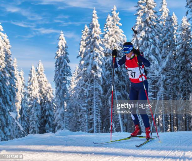 shot of young female biathlon competitor at cross country skiing - sport invernale foto e immagini stock