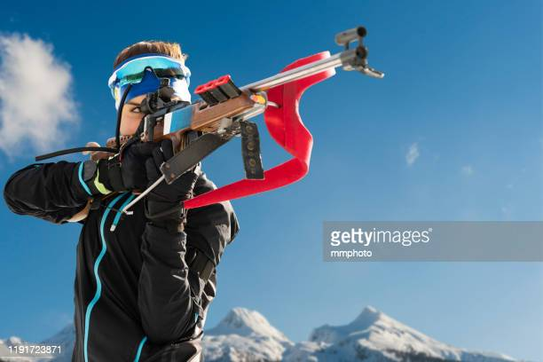 shot of young female biathlon competitor target shooting - sport invernale foto e immagini stock