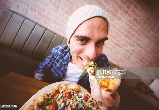 Shot of young man biting a slice of pizza