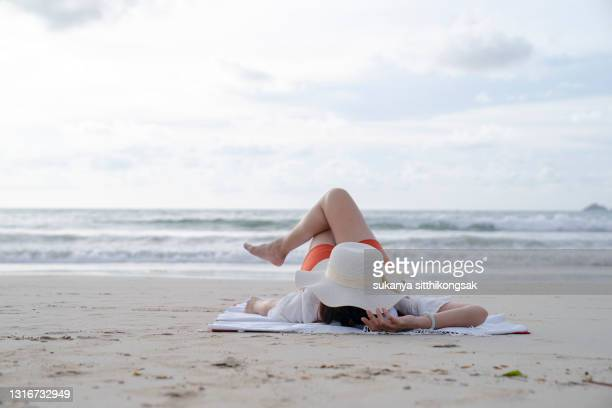 shot of young woman arms outstretched lying on a mat,relaxing and sunbathing at the beach. - one mature woman only stock pictures, royalty-free photos & images