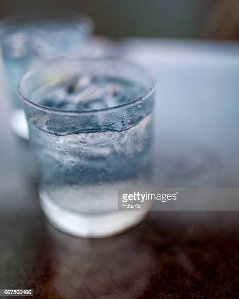 Shot outside, a close up of two glasses of cold gin & tonic with a lime wedge and ice cubes in each one.