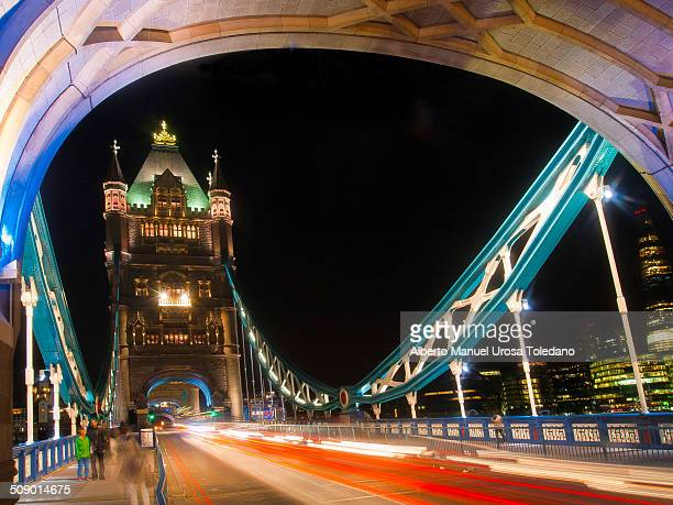 Shot taken in Tower Bridge by night. It is poassible to see a few people and because it was with a long exposure, there are trails of car lights.