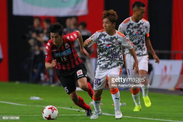 Shota Kaneko of Shimizu SPulse and Naoya Kikuchi of Consadole Sapporo compete for the ball during the JLeague J1 match between Consadole Sapporo and...
