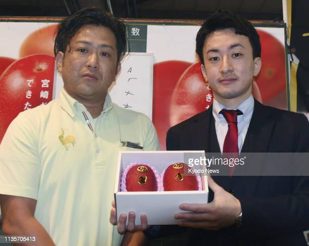 Shota Tatemoto , an employee of a fresh produce wholesale company, poses for a photo after making the 500,000 yen record winning bid for a pair of...