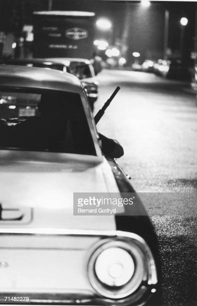 A shotgun and an elbow protrude from the window of a police cruiser on a city street at night during the suppression of rioting Newark New Jersey...