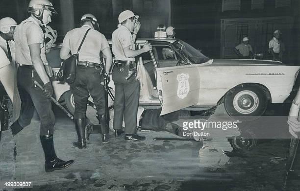 Shotgun blast victim Patrolman Joseph Hennigan lies by a squad car as racial rioting flared for the second straight night in Buffalo's Negro ghetto...