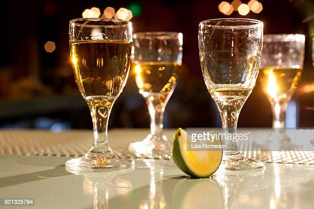 Shots of various types of tequila on bar with lime wedge