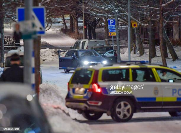 A shotup car stands behind police cordons where two men were found with gunshot wounds in Kista Northwestern Stockholm on late March 8 2017 Both men...