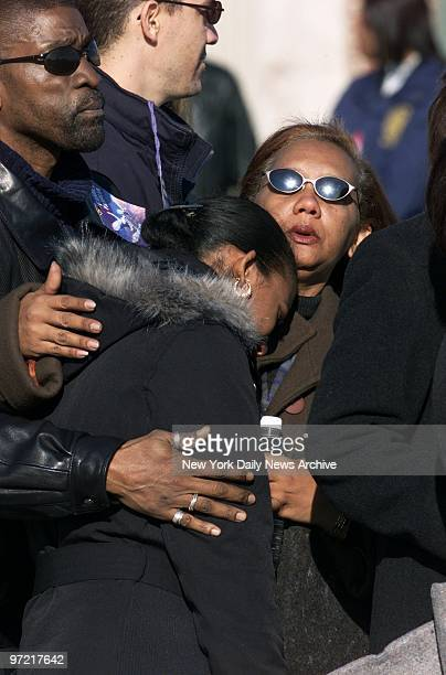 A shoulder to lean on and a pat on the back offer welcome comfort to one griefstricken woman during a prayer service for victims of the crash of...