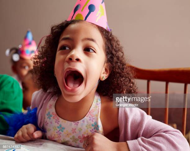 shouting girl wearing party hat with mouth open - girls open mouth stockfoto's en -beelden