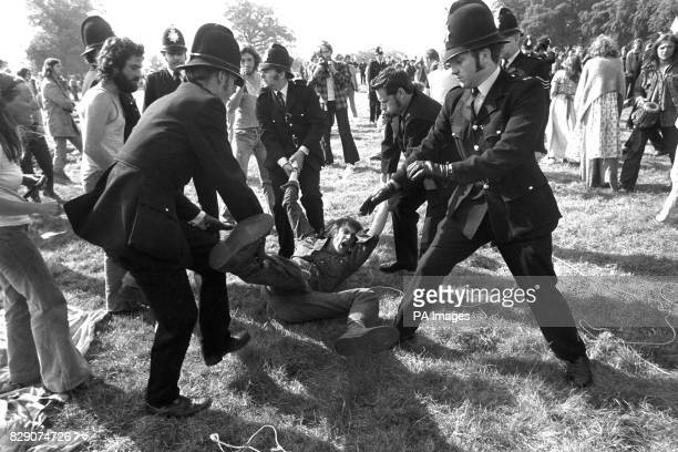 A shouting man in the grip of the law as police moved to disperse groups of fans still in Windsor Great Park after a swoop of over 600 policemen had...