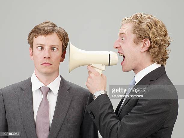 shouting through megaphone at another man