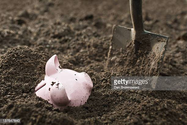 Shovel digging up piggy bank
