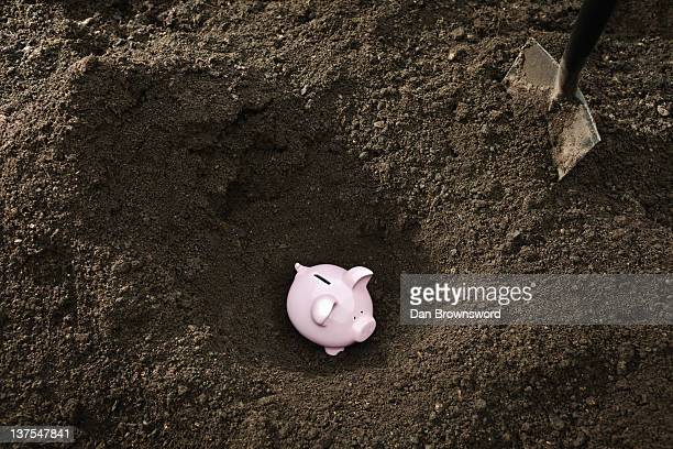 shovel digging up piggy bank - enterrar imagens e fotografias de stock