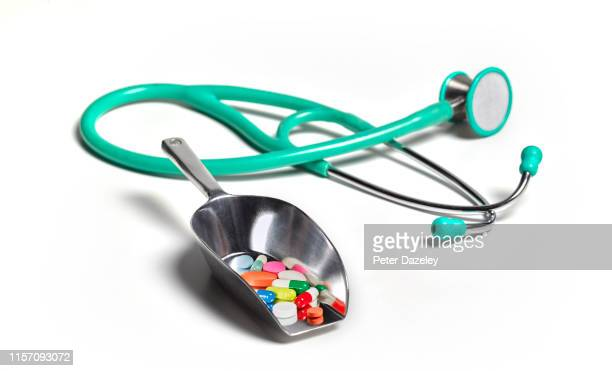shovel full of pills with stethoscope - ibuprofen stock pictures, royalty-free photos & images