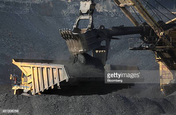 A shovel loader loads a mining truck with coking coal during mining operations in the open pit at the Neryungrinsky mine operated by OAO Mechel in...