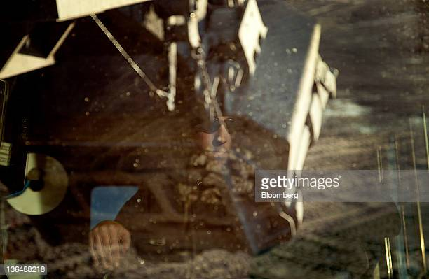Shovel operator Carl Senarighi is reflected in the window of a PH electric rope shovel while digging taconite out of an open pit mine at the Hibbing...