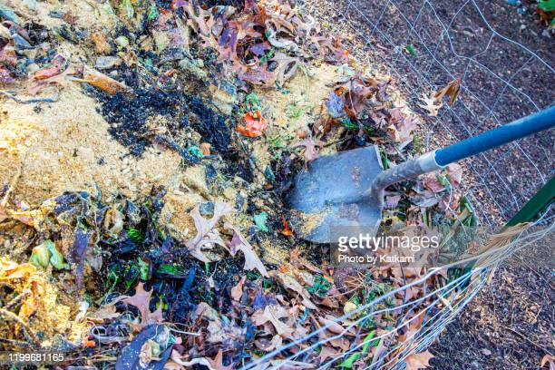 shovel turning compost pile - turning stock pictures, royalty-free photos & images